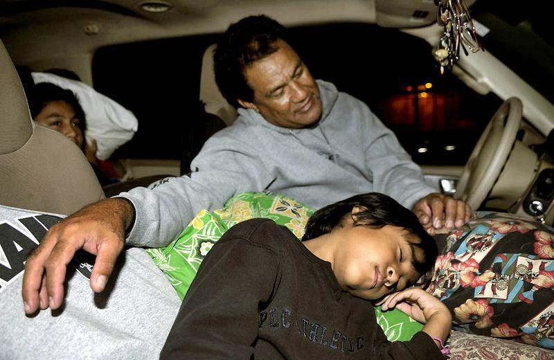 Пуипуи Фалетой (на заднем плане в центре) с сыновьями Дэниелом (слева) и Флетчером на парковке в Оаху, Гавайи. Это место было подготовлено в качестве центра Красного креста для возможных пострадавших от последствий цунами. (Rebecca Breyer/Associated Press)