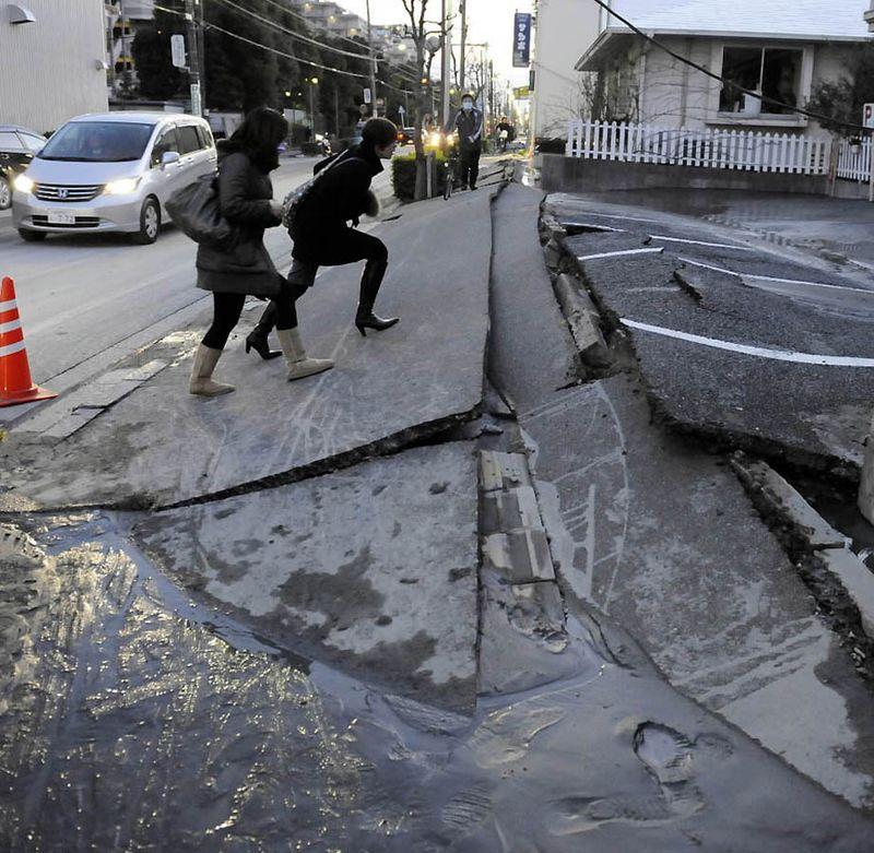 Прохожие на разрушенной дороге после землетрясения в Урауасу, префектура Чиба. (Toshifumi Kitamura/AFP/Getty Images)