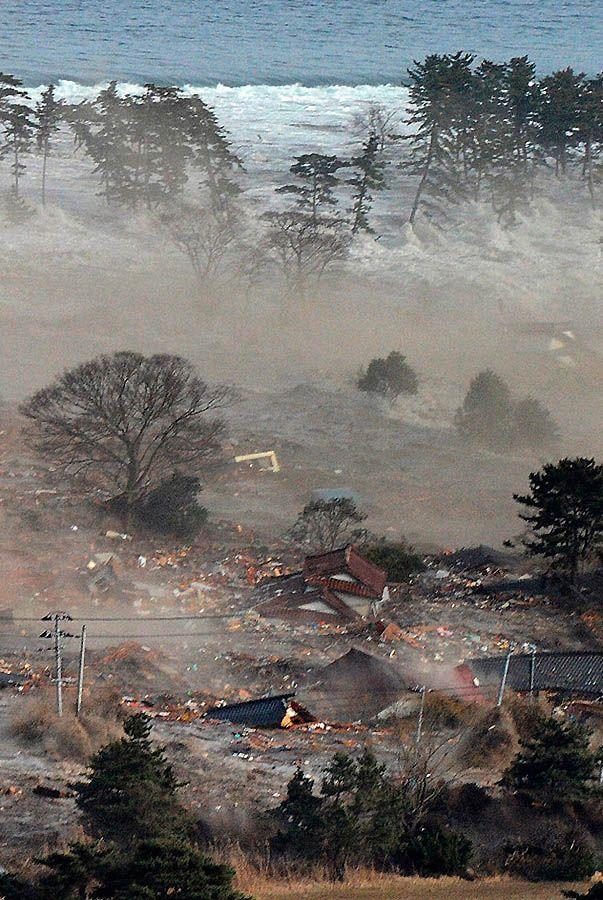 Цунами сметает дома в городе Натори. (REUTERS/KYODO)