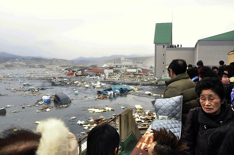 Люди смотрят на последствия цунами в порту Кесеннума в префектуре Мияги. (AP Photo/Keichi Nakane, The Yomiuri Shimbun)