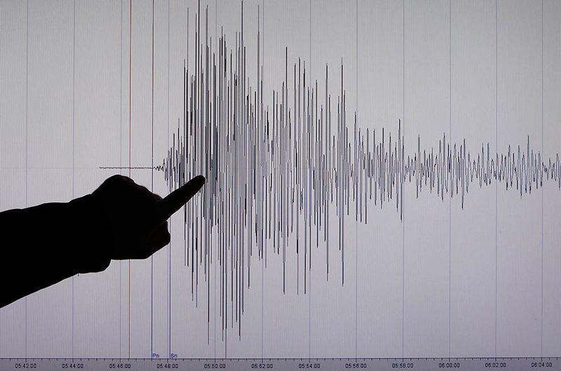 Сейсмолог Бернд Вебер из немецкого исследовательского института в Потсдаме указывает на шкалу силы землетрясения в Японии. (REUTERS/Fabrizio Bensch)