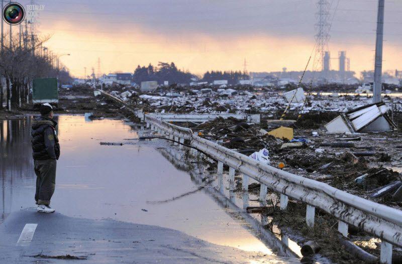 Человек смотрит на вызванные последовавшим за землетрясением цунами разрушения в городе Сендай на северо-востоке Японии, 12 марта 2011 года.