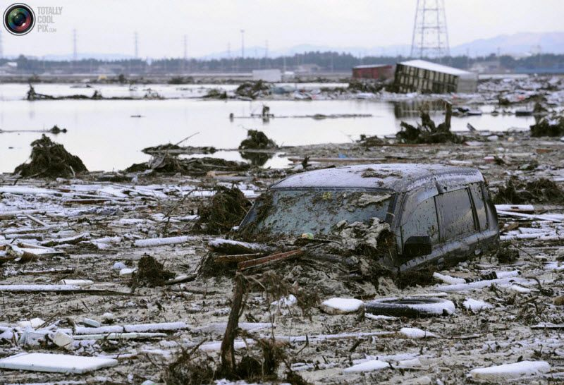 Сендай, 12 марта 2011 года. Машина, засыпанная мусором.