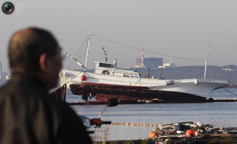 Человек смотрит на рыболовецкое судно, пострадавшее из-за цунами в порту города Оарай, на северо-восток от Токио, 12 марта 2011 года