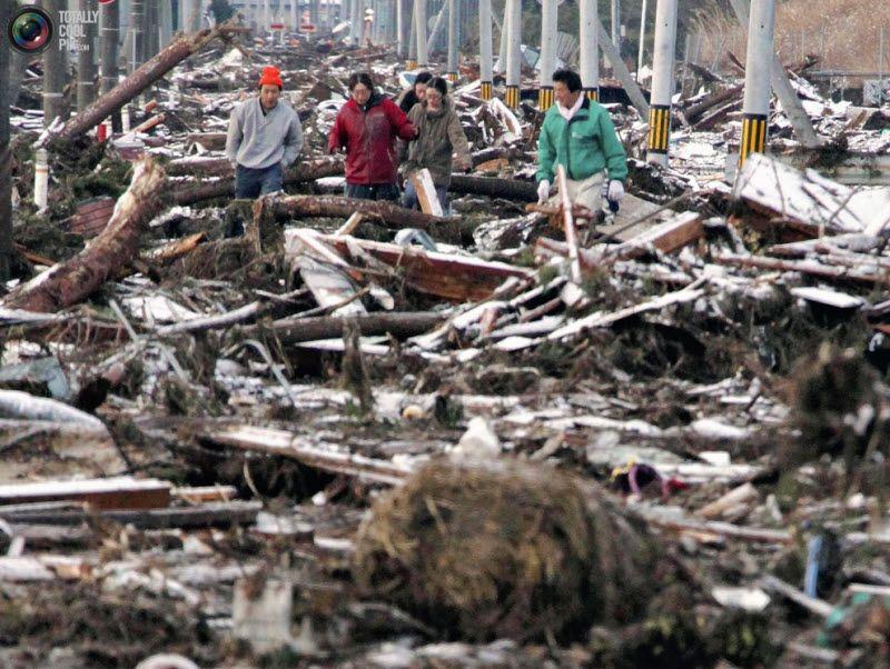 Люди пытаются пройти по превратившейся в развалины улице, Сендай, префектура Мияги, 12 марта 2011 года.
