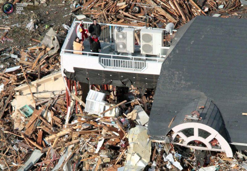 Люди ждут спасения на крыше здания, префектура Иватэ, северо-восток Японии, 12 марта 2011 года.