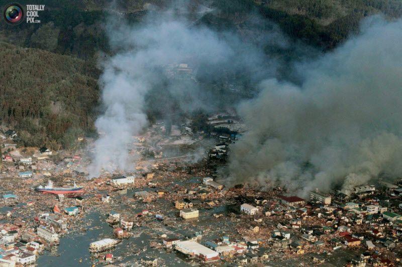 Дым над жилым районом в Сендай, северо-восток Японии, 12 марта 2011 года.
