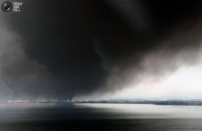 Густой черный дым над городом в префектуре Мияги, 12 марта 2011 года.