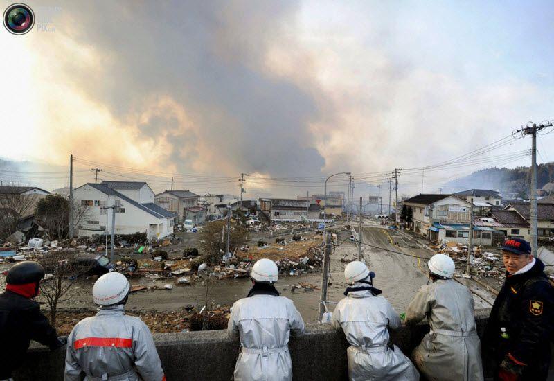 Пожарные смотрят на поднимающийся над городом дым, префектура Мияги, северо-восток Японии, 12 марта 2011 года.