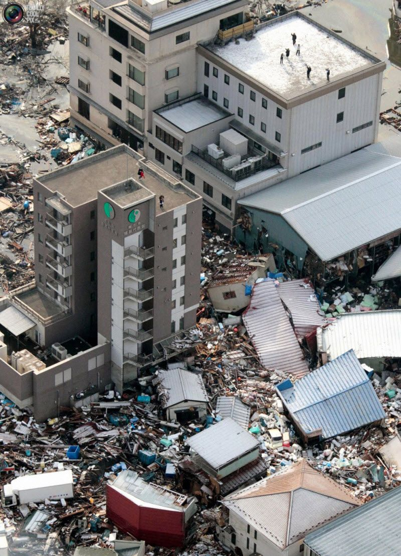 Люди ждут спасателей на крыше дома в префектуре Мияги.