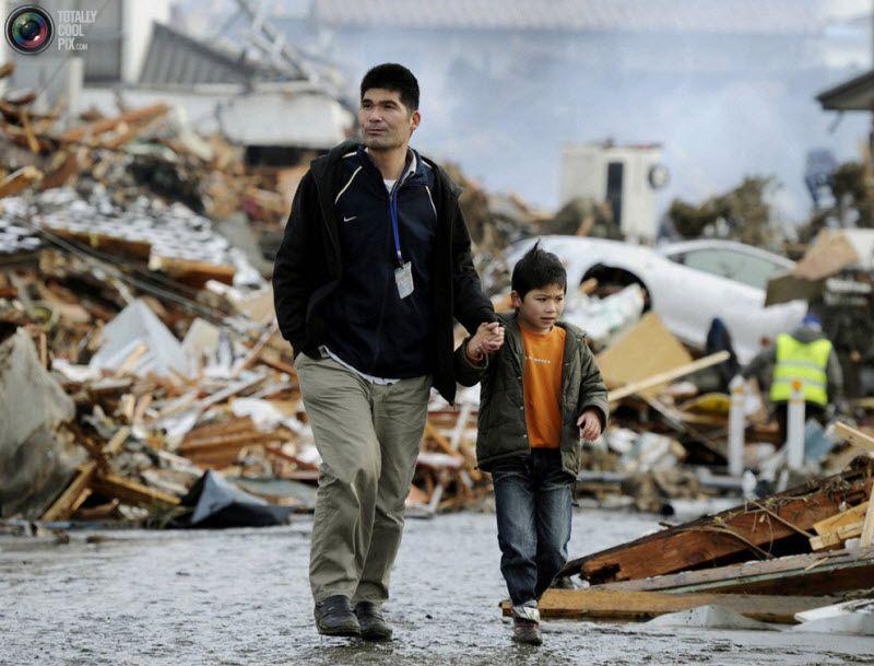 Мужчина и мальчик среди развалин домов, Сендай.