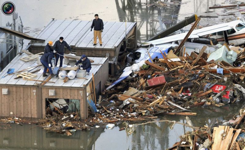 Люди строят плот на крыше дома в аэропорту Сендай, 12 марта 2011 года.