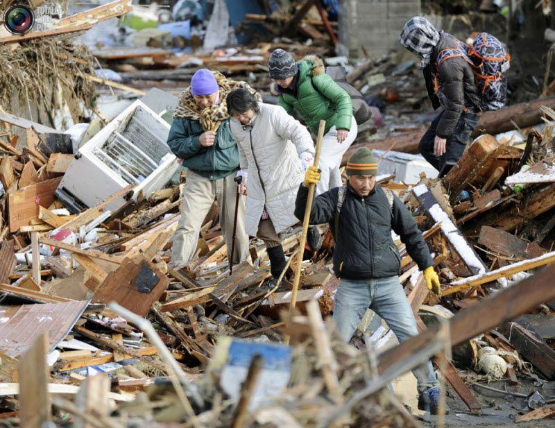 Люди среди развалин жилых домов в Сендай, 12 марта 2011 года.