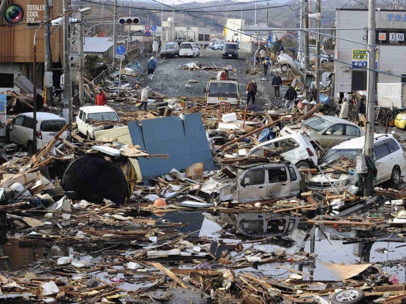 Автомобили и разрушенные дома в Кесеннума, префектура Мияги.
