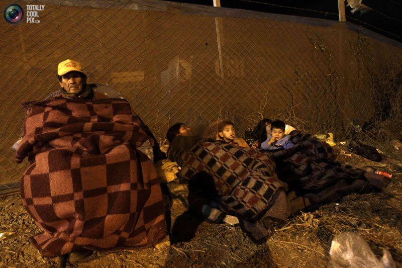 Семейство готовится ко сну под открытым небом на вершине холма после того, как правительство Чили объявило об эвакуации прибрежных районов в порту Сан-Антонио, 11 марта 2011 года. О возможности цунами было объявлено после того, как накрывшее Японию цунами добралось до Гавайев.