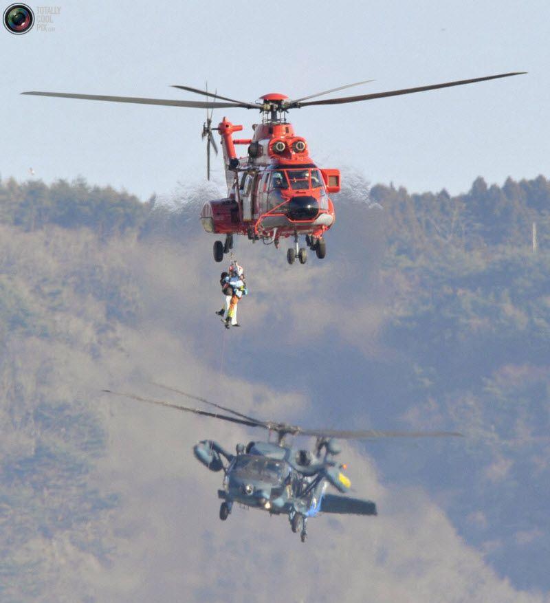 Оказавшегося запертым в здании японца спасает вертолет, город Кесеннума, префектура Мияги, 12 марта 2011 года.