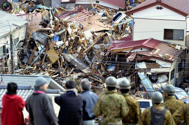 Люди смотрят на разрушенные дома в городе Кесеннума, префектура Мияги, 12 марта 2011 года.