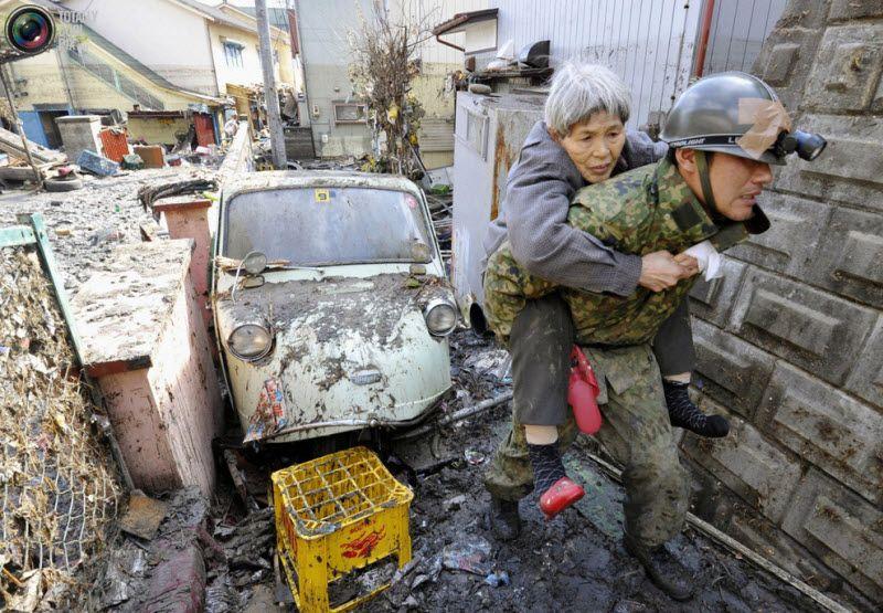 Женщину, оказавшуюся в ловушке в собственном доме, спас солдат, Кесеннума, префектура Мияги, 12 марта 2011 года.