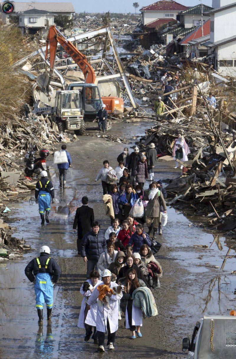 Люди идут в эвакуационный центр в городе Натори, префектура Мияги.