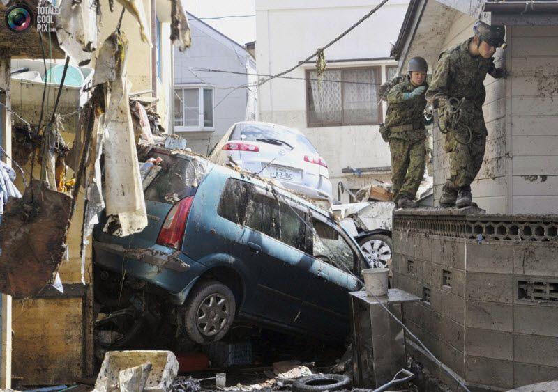 Солдаты войск самообороны пытаются по стене обойти развалины машины, город Кесеннума, префектура Мияги.