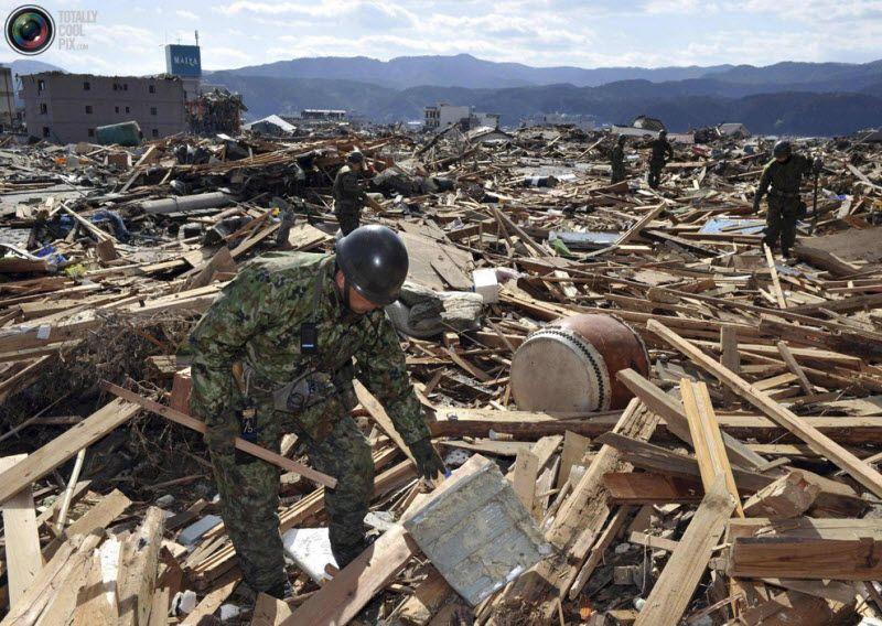 Солдаты войск самообороны ищут пропавших без вести в городе Рикузентакаташи в префектуре Иватэ на северо-востоке Японии, 12 марта 2011 года.
