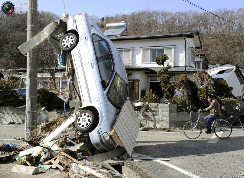 Перевернутая цунами машина на улице Мияко, префектура Иватэ, 12 марта 2011 года.