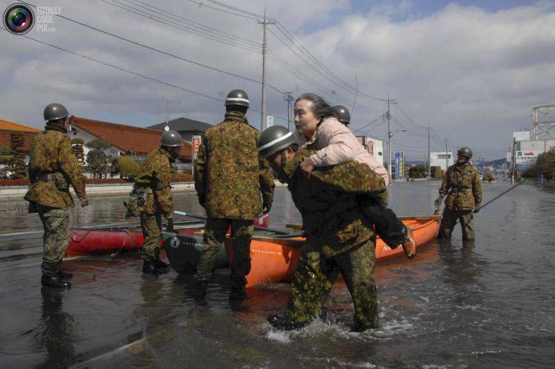 Солдаты войск самообороны спасают женщину в городе Исиномаки в префектуре Мияги, 12 марта 2011 года.
