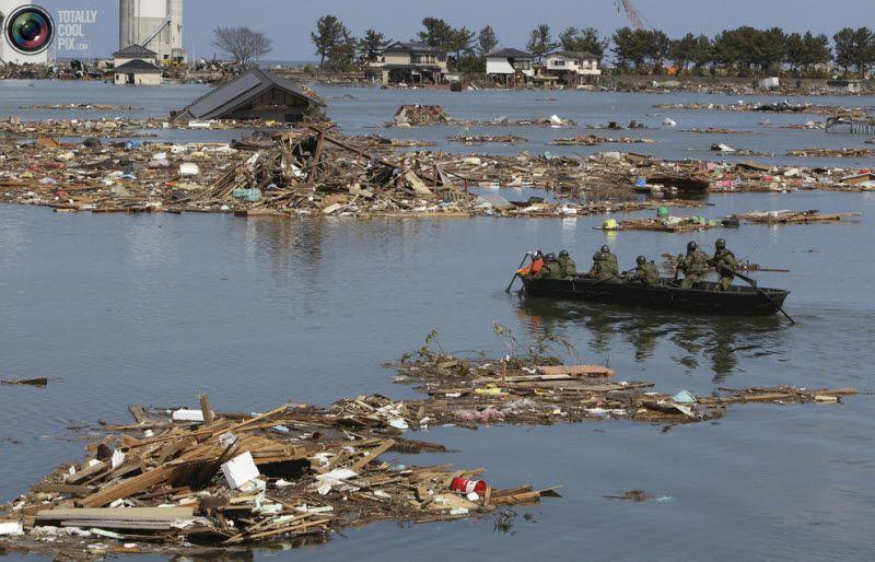 Солдаты войск самообороны на лодке ведут поиск пострадавших, город Соума, префектура Фукусима, 12 марта 2011 года.