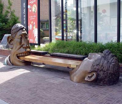 Памятник: мужчины держат зыбами скамейку