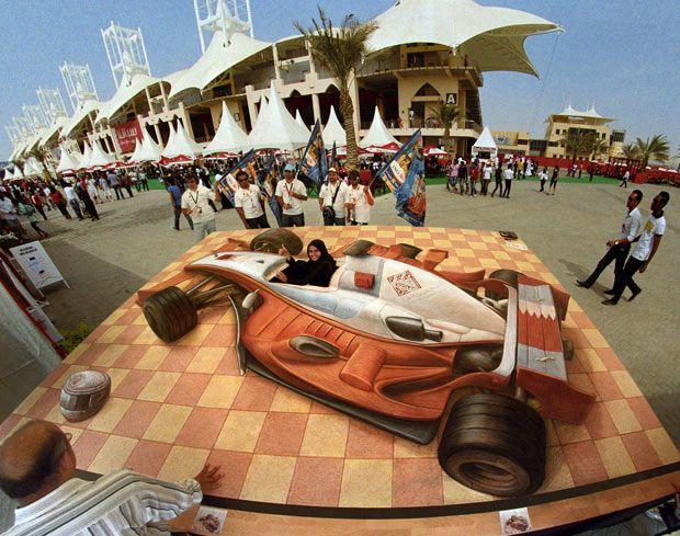 Женщина – водитель в Бахрейне, март 2008 года. У этого изображения гоночного автомобиля F1 <br> было вырезано отверстие для публики, чтобы удобнее было фотографироваться.