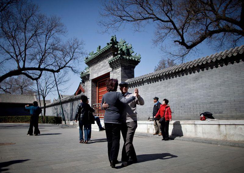 Китайцы отрабатывают танцевальные движения в парке недалеко от ворот Тяньаньмэнь в Пекине. (Andy Wong/Associated Press)