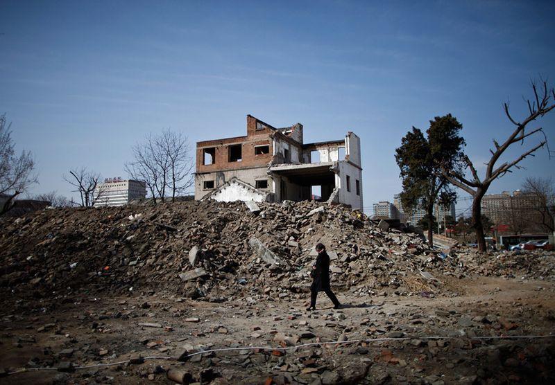 Девушка идет среди обломков частично снесенного здания. (Andy Wong/Associated Press)