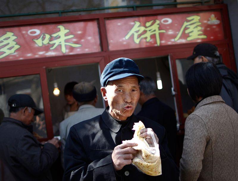 Китаец у продуктового магазина в Пекине. (Andy Wong/Associated Press)