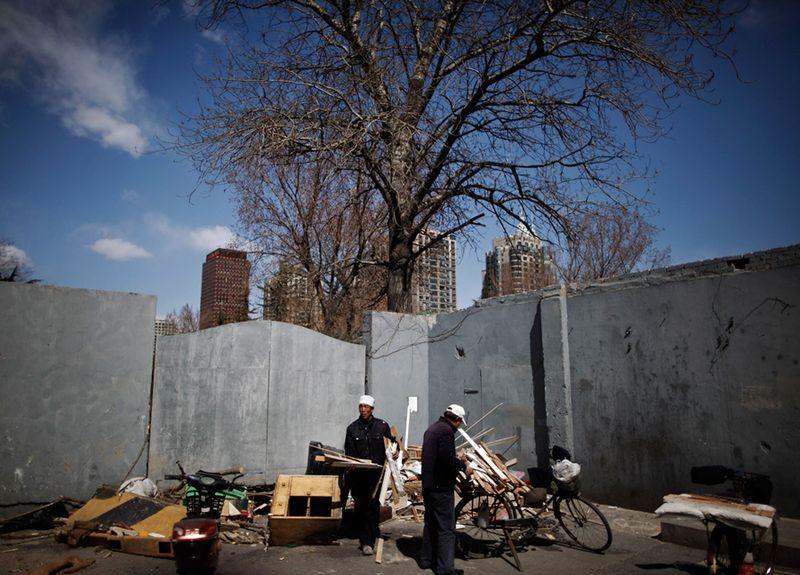 Китайцы собирают куски разбитой мебели недалеко от жилого комплекса в Пекине. (Andy Wong/Associated Press)