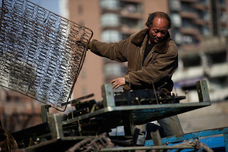 Мусорщик отбирает металлический лом на свалке в Шанхае. (Eugene Hoshiko/Associated Press)