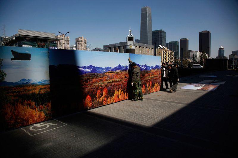 Рабочие закрепляют забор вокруг стройплощадки в Пекине. (Ng Han Guan/Associated Press)