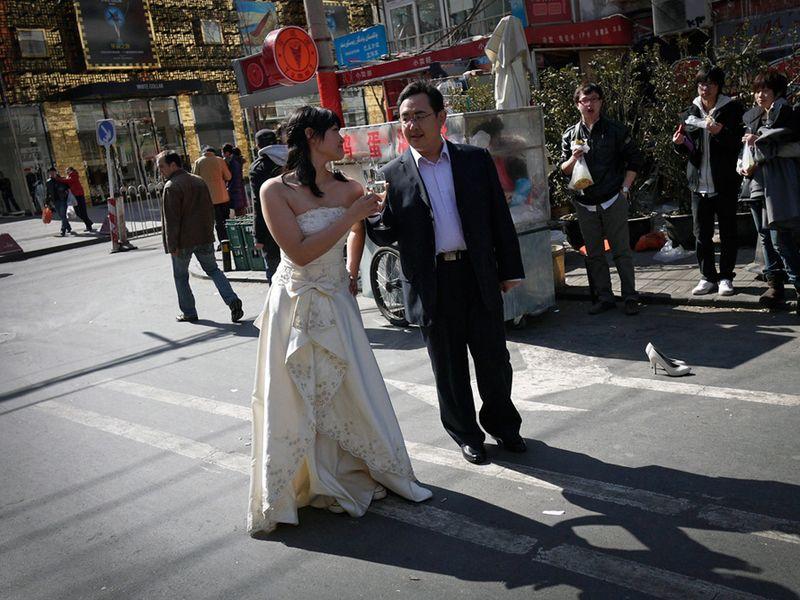 Новобрачные с шампанским на фоне торгового центра в Пекине. (Andy Wong/Associated Press)
