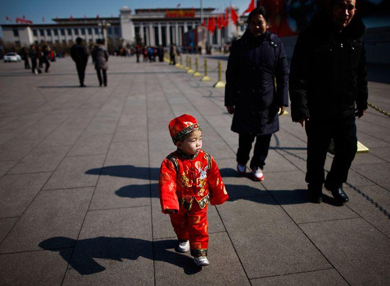 Ребенок в народном костюме с родителями на площадь Тяньаньмэнь в Пекине. (Andy Wong/Associated Press)