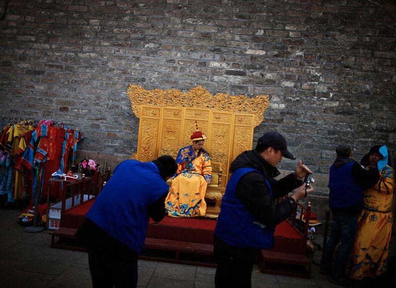 Китайский турист в костюме императора на фотосессии недалеко от улицы Цяньмэнь в Пекине. (Andy Wong/Associated Press)