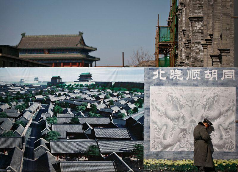 Охранник возится с мобильником рядом с рекламным щитом с планом застройки района в Пекине. (Andy Wong/Associated Press)