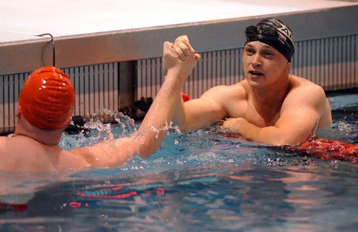 Солдат Гэвин Сибайен поздравляет морского пехотинца Джеймса Кребса в победе на дистанции 100 метров вольным стилем.