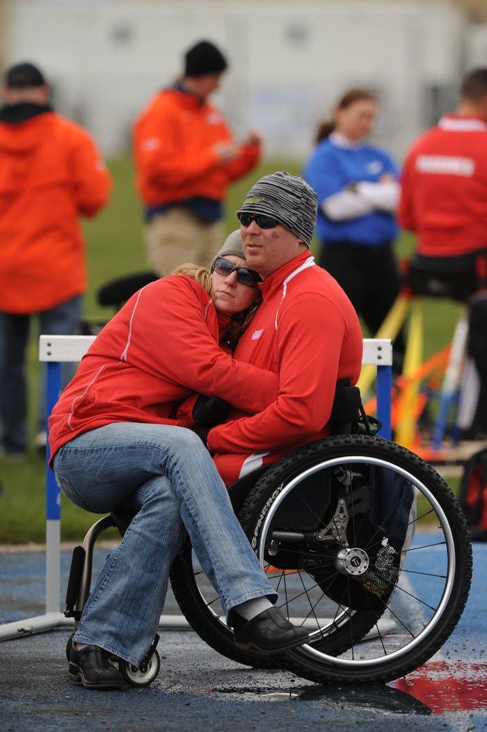 Джилл Грин на коленях у мужа. Семья наблюдает соревнования по легкой атлетике.