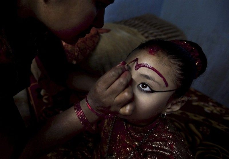 1. Пурна Шова Башарйа, мать Кумари Саммиты Байрашарйа,  накладывает макияж на лицо девочки для участия в торжественной процессии в Кумари Гхар в городе Патан, Непал, 7 апреля.