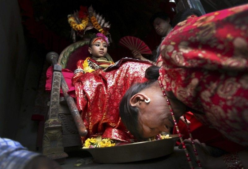 4. Верующие поклоняются Кумари во время религиозного фестиваля в городе Патан, 19 апреля.<br>Кумари большую часть времени остается практически заключенной в собственном доме, но есть некоторые дни, когда ей разрешено появиться перед публикой. Тем не менее,  из дома ее должны вынести, сама выйти она не может, ее ноги  не должны коснуться земли, так как это считается плохим предзнаменованием. Верующие просят ее благословения, даря ей цветы, деньги и прикасаясь к ее ногам. Все, начиная от  бизнесменов, которые хотят начать новый проект, студентов, которые  готовятся к важному экзамену, и заканчивая просто людьми, надеющимися найти силы и вымолить улучшения здоровья больного посещают Кумари в Кумари Гхар для того, чтобы получить ее благословения.