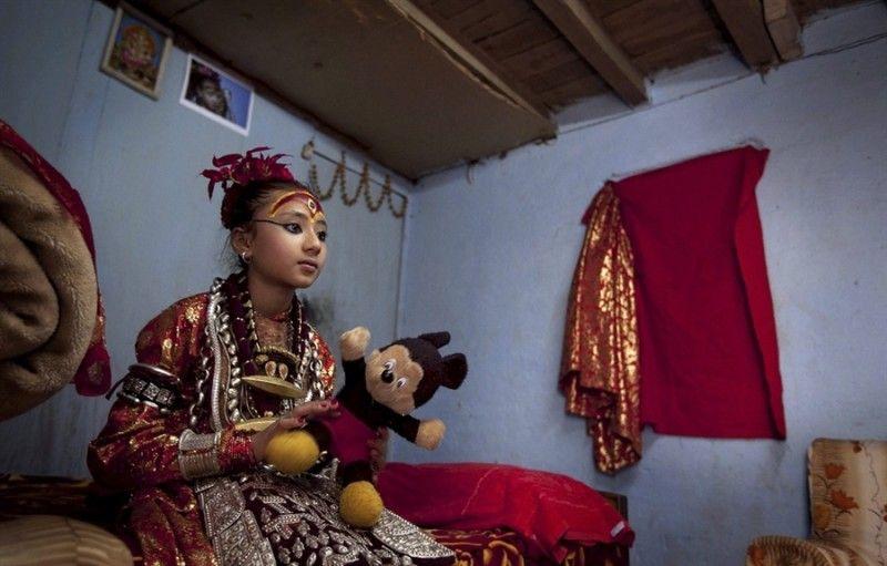 6. Богиня Кумари с игрушечным Микки-Маусом. В выходные ее друзья  имеют право навещать ее.<br>Саммита Байрашарйа останется Кумари до тех пор, пока у нее впервые не начнется менструация. Считается, что после этого богиня покидает ее тело, и начинается поиск новой маленькой девочки, которая должна стать воплощением богини Кумари.