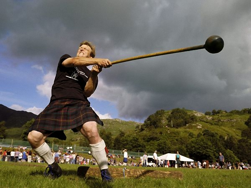 Состязания в горах Шотландии. Участник игр, одетый в традиционный шотландский килт, состязается в <br> метании молота, в конкурсе который проводится в Гленфиннане. Традиционные шотландские игры состоят <br> из состязаний, танцев, еды и напитков, чтобы отдохнуть от трудовых будней. (Jin Richardson).