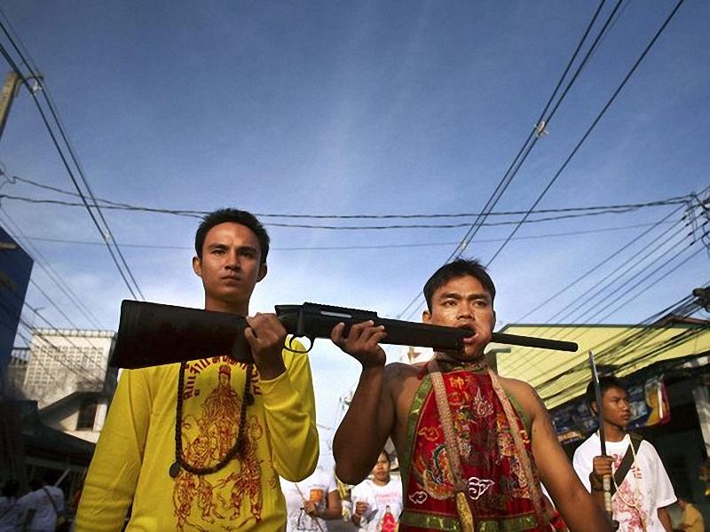 Вегетарианский фестиваль, Таиланд. Верующие храма на Bang Neow, участвуют в параде вегетарианского фестиваля на <br> острове Пхукет в Таиланде, втыкают оружие в себя, в знак протеста. Китайские иммигранты дали начало этой даосской <br> церемонии в 1825 году, когда люди, верящие в бога, ели вегетарианскую пищу, чтобы спастись от эпидемии. (David Longstreath/AP).