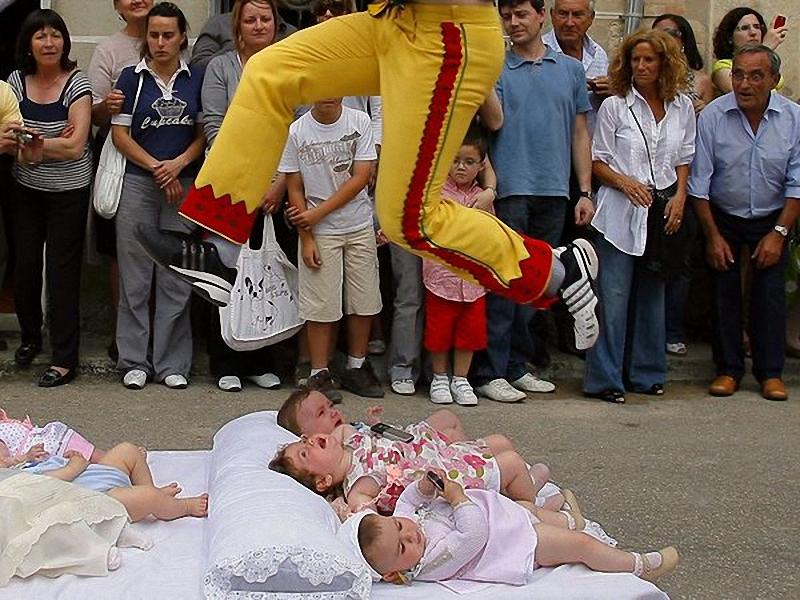 Празднование Тела Христа (Corpus Christi), Испания. Человек в маске, известный как El Colacho, символ Сатаны, перепрыгивает <br> через группу девочек. Многовековой ритуал предназначен для защиты детей от злых духов. Празднование Chorpus Christi, проводится <br> каждый год в Кастрильо-де-Мурсия, Испания, и отдает дань католическому празднованию Святого Причастия. (Israel L. Murillo/AP).