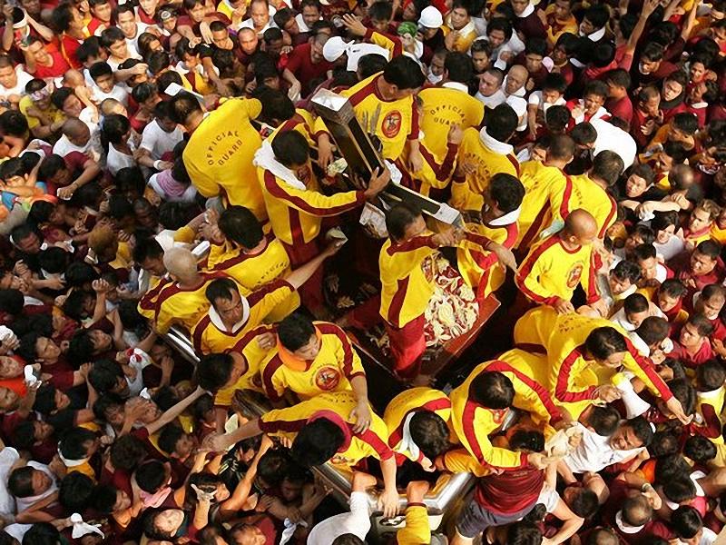 Праздник Черного Назарянина, Филиппины. Во время парада по улицам Манилы верующие осаждают огромное изображение Христа, Черного Назарянина. <br> Каждый год этот праздник привлекает сотни тысяч христиан, большинство из которых идут босиком, а также оставляют свою одежду организаторам, <br> в надежде, что их вещами протрут статую и вернут законным владельцам. Вера в сверхъестественные возможности статуи продолжается уже 400 лет, <br> возможно, из-за ее невероятной истории. Во время путешествия из Мексики в 1606 году, на лодке, которая везла статую, вспыхнул пожар, но, <br> статуя, хотя и почерневшая, была спасена. (Aaron Favila / AP).