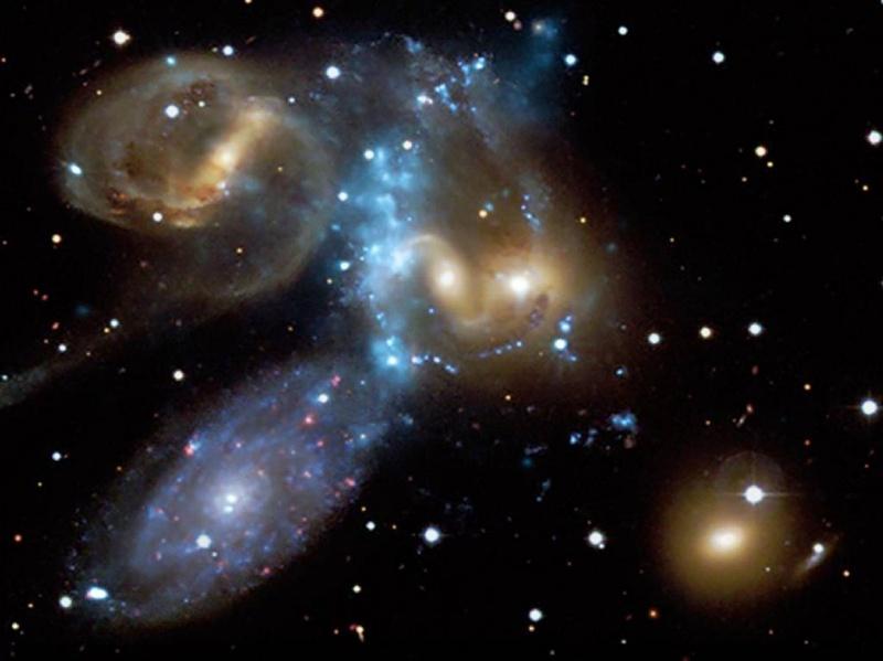 Квинтет Стивена – это компактная группа галактик, открытая около 130 лет назад и расположенная примерно в 280 миллионах световых лет от Земли. Этот снимок, опубликованный 9 июля, сочетает в себе изображение в видимом свете (с помощью телескопа Канада-Франция-Гавайи) и с помощью рентгеновских лучей (из обсерватории Чандра). Голубая полоса в центре изображения представляет собой взрывную волну рентгеновских лучей, возникших из-за крушения галактик. (NASA/CXC/CfA/CFHT)